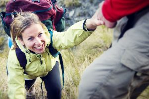 47064437 - couple hiking helping climbing mountain concept